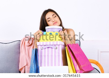 Beautiful young woman with shopping bags and boxes sitting on sofa in room - stock photo