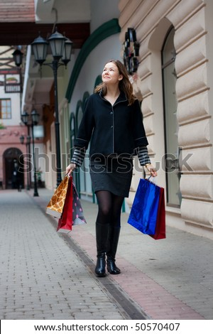 beautiful young woman with shopping bags walking outdoors - stock photo