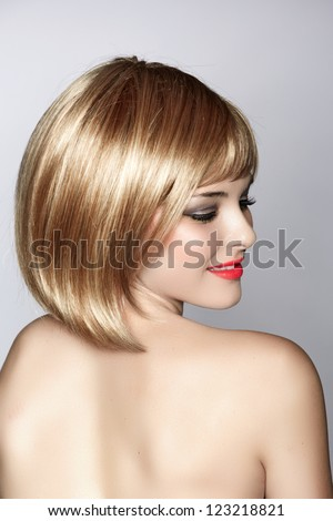 beautiful young woman with short blond hair in a bob wearing red lipstick on studio background - stock photo
