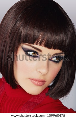 beautiful young woman with short brown hair in red blouse wearing smoky purple eyeshadow and dramatic eyeliner. - stock photo