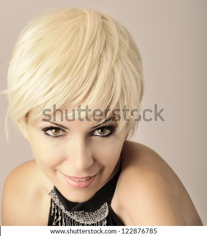Beautiful young woman with short pixie light blond hair looking at camera and smiling - stock photo