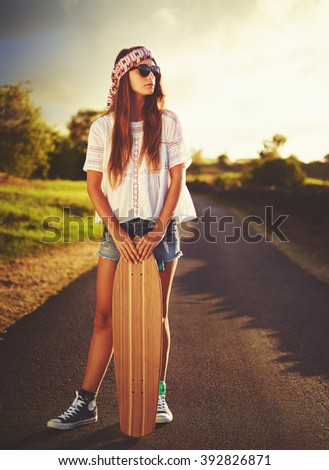 Beautiful young woman with skateboard on country road at sunset - stock photo
