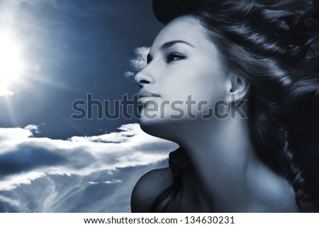 beautiful young woman with sky and sun in background blue color