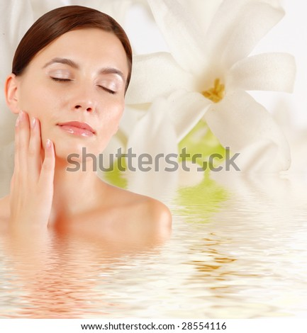 Beautiful young woman with sprig flower  reflected in water - stock photo