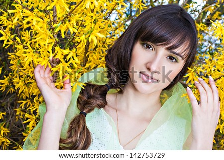 Beautiful young woman with spring yellow blossom