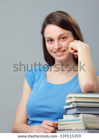 Beautiful young woman with stack of books
