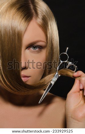Beautiful young woman with straight hair holds scissors - stock photo