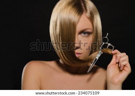 Beautiful young woman with straight hair holds scissors