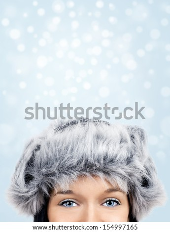 Beautiful young woman with stunning eyes and fur hat over winter snow background - stock photo