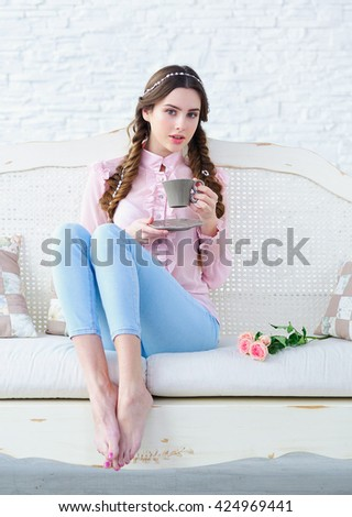 Beautiful young woman with stylish braids hairstyle enjoying a cup of her morning coffee with comfort on a sofa - stock photo