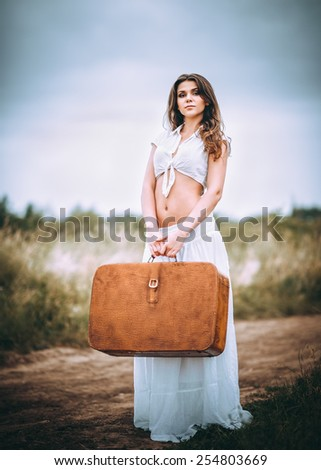 Beautiful young woman with suitcase in hands stands on a field road - stock photo