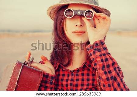 Beautiful young woman with suitcase looking through binoculars. Image with instagram color effect