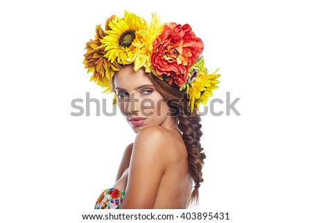 Beautiful Young Woman with Summer  Flowers. Long Permed Curly Hair and Fashion Makeup. Beauty Girl with Flowers Hairstyle.