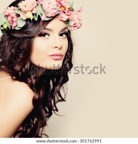 Beautiful Young Woman with Summer Pink Flowers. Long Permed Curly Hair and Fashion Makeup. Beauty Girl with Flowers Hairstyle.  - stock photo