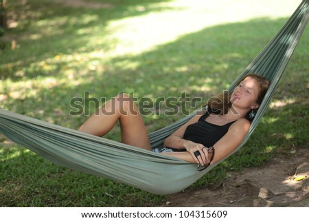 Beautiful young woman with sunglasses in her hand resting in a hammock in the shade - stock photo