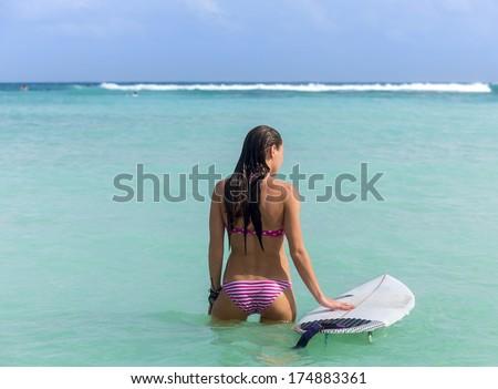 Beautiful young woman with surfboard in sexy bikini in ocean - stock photo