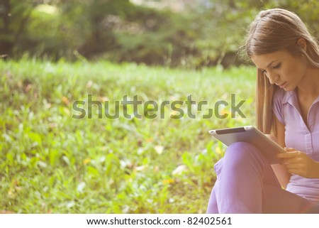 Beautiful Young Woman With Tablet Computer In Park - stock photo