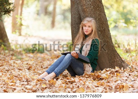 Beautiful young woman with tablet in autumn park
