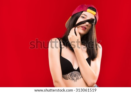 Beautiful young woman, with tattoo on her chest, wearing on claret cap and black bra, posing on the red background, in studio, waist up - stock photo