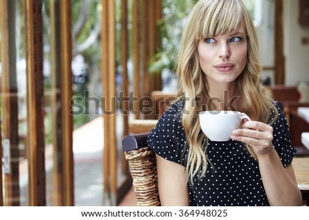 Beautiful young woman with teacup in cafe - stock photo