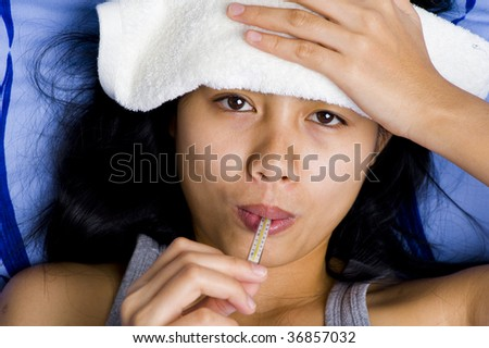 beautiful young woman with thermometer in mouth having fever - stock photo