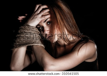 Beautiful young woman with tied arms over black background - stock photo