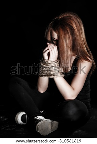 Beautiful young woman with tied arms sitting on the floor over black background - stock photo
