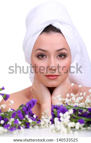 Beautiful young woman with towel on her head and flowers isolated on white - stock photo