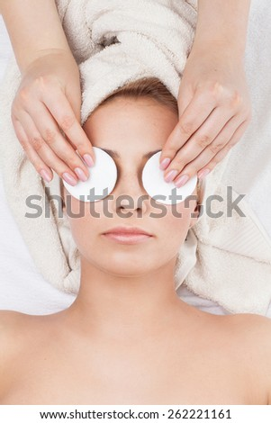 Beautiful young woman with towel on her head lying in spa salon - stock photo