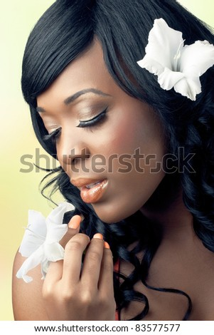Beautiful young woman with tropical flowers in her hair and hands, close-up shot - stock photo