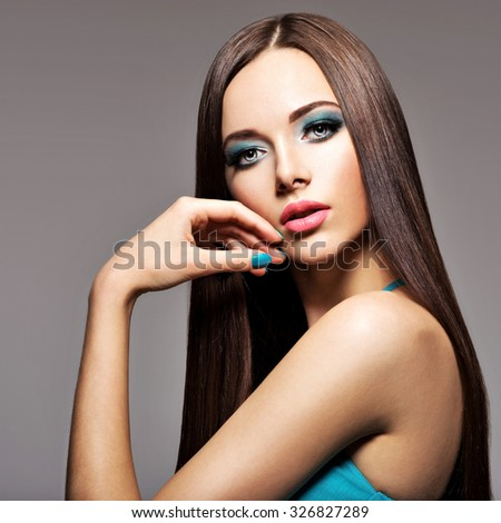 Beautiful young woman with turquoise makeup and long hairs - posing at studio - stock photo