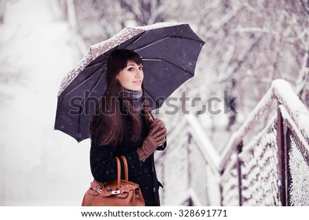 Beautiful young woman with umbrella in snowfall toned image - stock photo