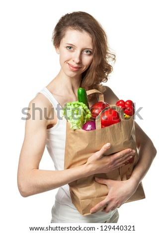 Beautiful young woman with vegetables and fruits in shopping bag; isolated on white