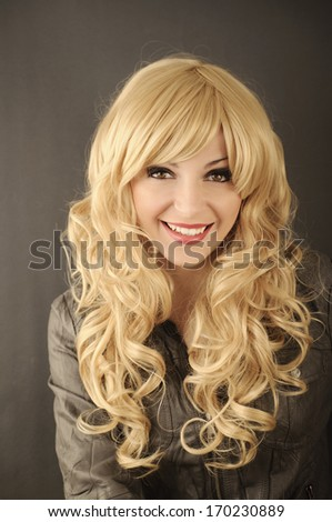 Beautiful young woman with wavy honey blond hair, smiling - stock photo