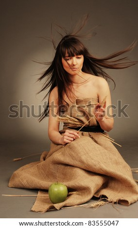 Beautiful young woman with wheat ears and green apple. Symbol of autumn. - stock photo