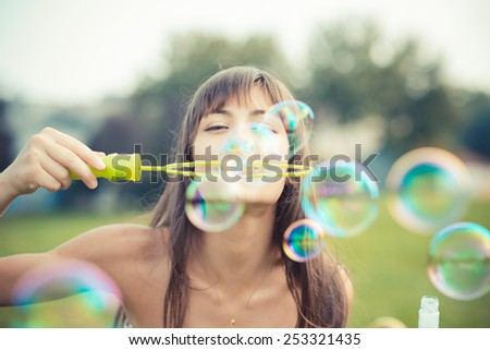 beautiful young woman with white dress blowing bubble in the city - stock photo