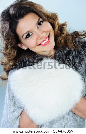 Beautiful young woman with white fur muff