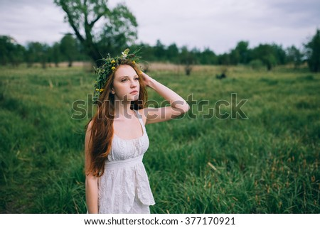 Beautiful young woman with wreath of wildflowers in their hair.