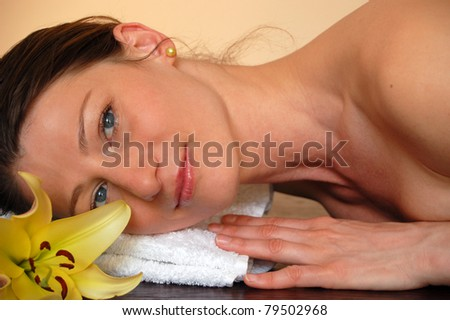 Beautiful young woman with yellow flower lying on white towel during a spa treatment, professional beauty makeup - stock photo