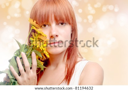 Beautiful young woman with yellow flowers over abstract blurred background - stock photo