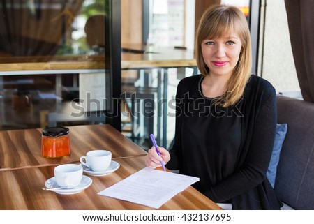 beautiful young woman woman drinking tea and working with business papers . breakfast in restaurant