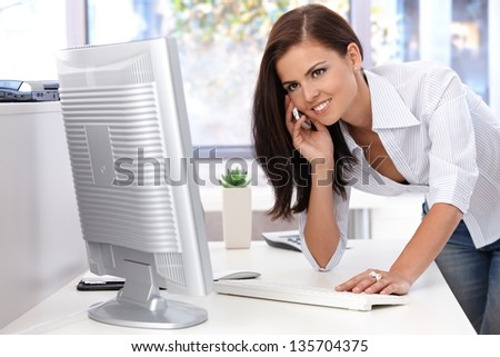 Beautiful young woman working in bright office, using mobile, smiling. - stock photo