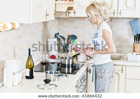 Beautiful young woman working in the kitchen - stock photo