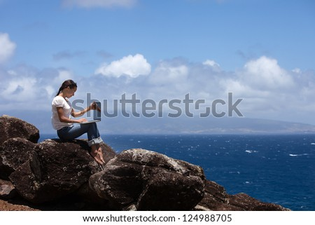 Beautiful young woman Working on a bluff in Hawaii - stock photo