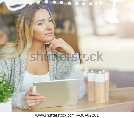 Beautiful young woman working on laptop and dreamily looking out the window at the cafe. Through glass
