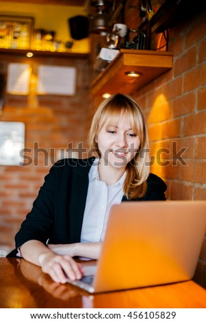 Beautiful young woman working on laptop at coffee bar.