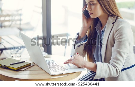 Beautiful Young Woman Working on Laptop in Coffee Shop