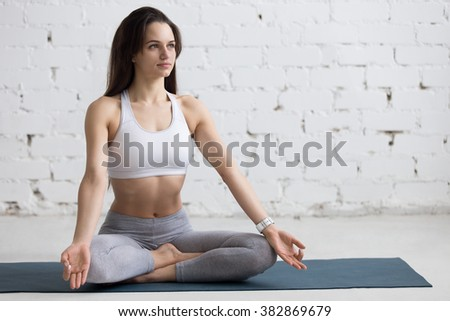 Beautiful young woman working out in loft interior, doing yoga exercise on blue mat, Sitting in Easy (Decent, Pleasant Posture), Sukhasana, asana for meditation, pranayama, full length, copy space - stock photo