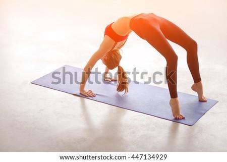 Beautiful young woman working out in loft interior, doing yoga exercise on blue mat, stretching, standing in Bridge Pose, Urdhva Dhanurasana Upward Bow, Chakrasana Wheel Posture, full length - stock photo