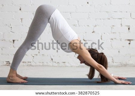 Beautiful young woman working out indoors, doing yoga exercise in the room with white walls, downward facing dog pose, adho mukha svanasana (sun salutation pose), full length, side view - stock photo
